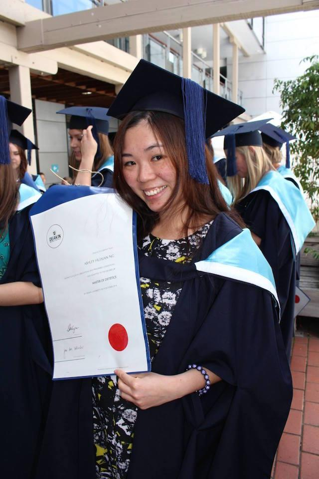 Ashley holding her diploma and in her graduation gown