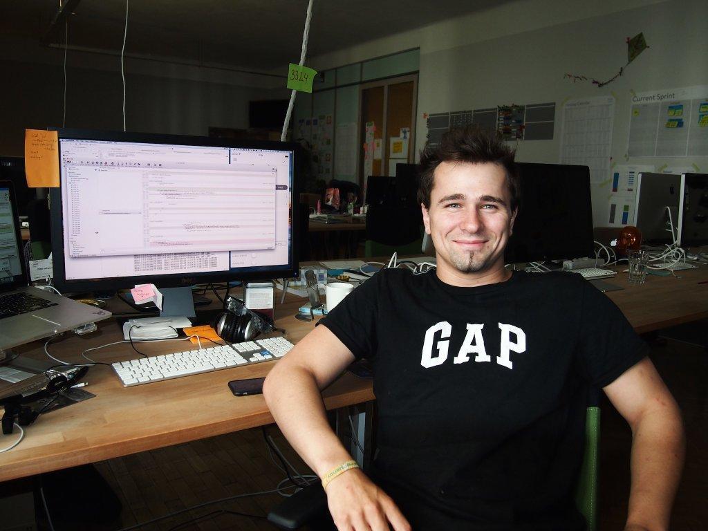 Lukas at his desk smiling at the camera
