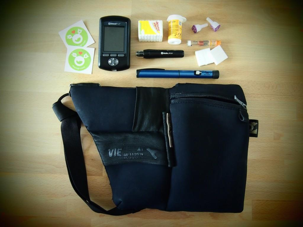 A cool urban carryall bag with some diabetes supplies around it