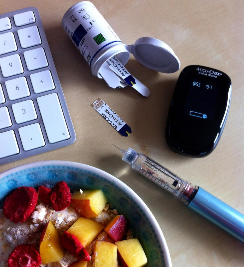 An insulin pen, meter, strips, keyboard, and a bowl of cereal with fruit