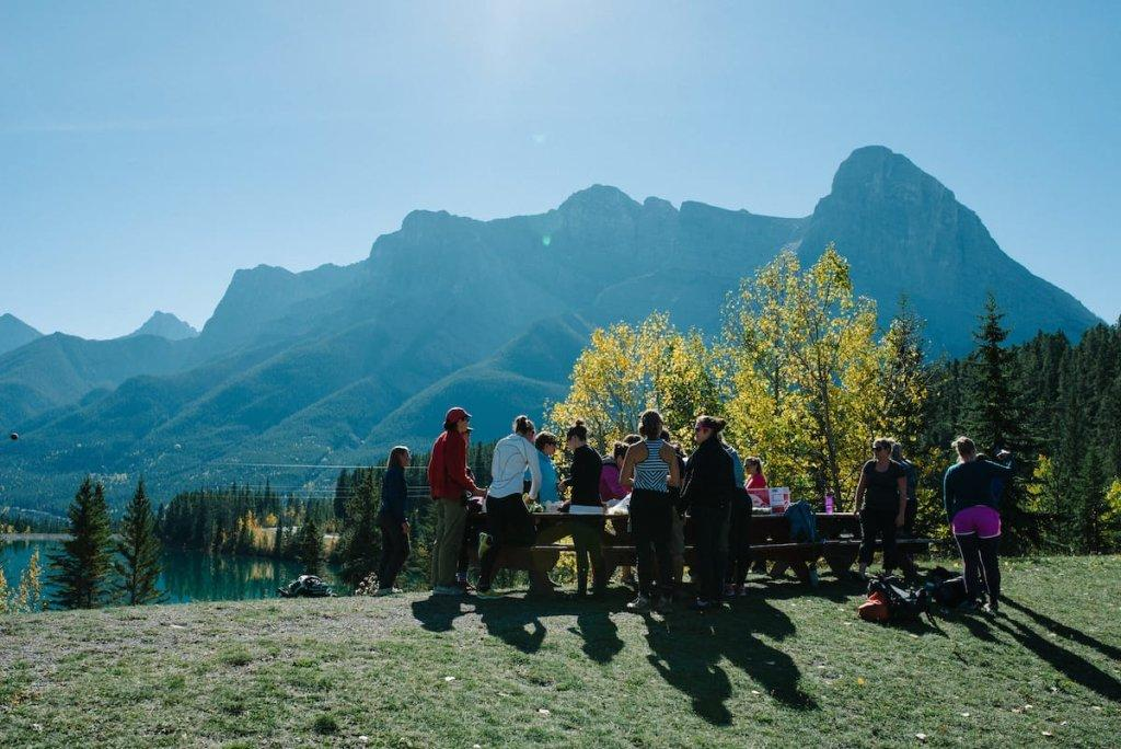 A group of people outside at a picnic table