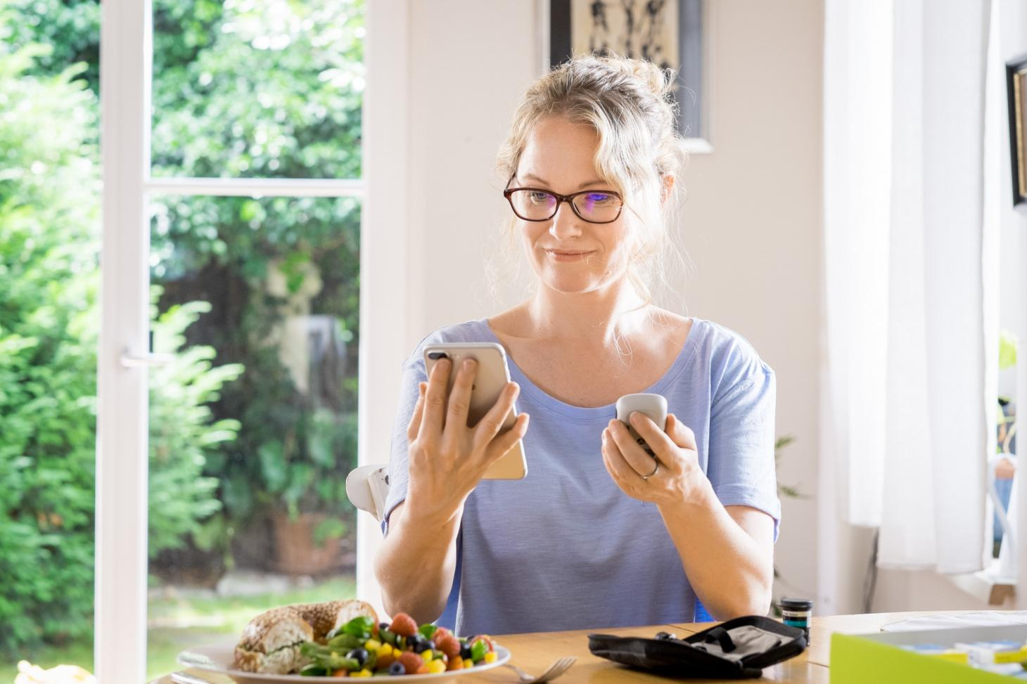 Woman wearing purple shirt and wearing glasses sitting at table next to window. Holding phone and Accu-Chek® Guide meter and there is a plate of food, half a bagel and a salad on the table. There are test strips on the table as well and the corner of the Bundle box.